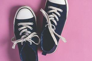 Dark blue Sneakers on pink  pastel background flat lay