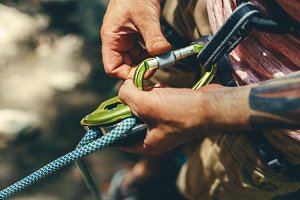 Unrecognizable man climbers check out climbing equipment outdoors