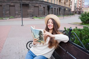 A young beautiful woman in an elegant hat sits on a bench in a new residential neighborhood and reads a paper book. She flips through the pages and smiles