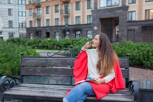 An attractive girl with long brown hair sits on a bench, hiding behind a red rug, gnawing a pen and thinking on an urban background. She has a notebook in her hands