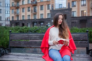 An attractive girl with long brown hair sits on a bench and writes her thoughts on the city background in a red notebook. She wears a white sweater, blue jeans and a red plaid