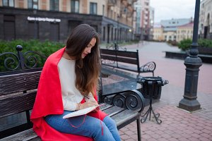 Attractive girl with long hair sits on a bench, covered in a red blanket, in a new residential quarter and writes her thoughts in a red notebook