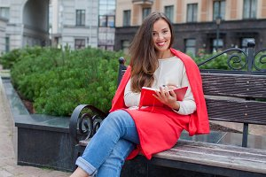 An attractive girl with long brown hair and a white tooth smile sits on a bench and writes her thoughts on the urban background in a red notebook. She is wearing a white sweater and blue jeans