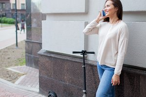 Beautiful young girl with long brown hair stopped while riding the scooter, to call a friend on the phone on the background of the gray wall. She is dressed in a white sweater and blue jeans