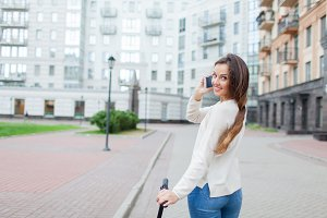 Beautiful young girl with long brown hair stopped while riding the scooter to talk to a friend on the phone on the background of the new residential quarter. Urban background