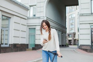 Beautiful, young, and white-toothed girl with long brown hair stopped while riding the scooter, to write to a friend on the phone. She is dressed in a white sweater and blue jeans. Urban background