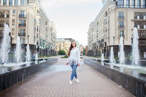 Young and beautiful girl walks by the fountain and smiling in a new residential complex
