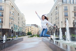 Young sporty girl jumping for joy at the fountain in the residential complex. Female in flight with his hands up