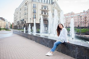 Young and beautiful girl sitting at the fountain and smiling in a new residential complex