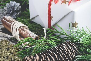 Christmas gift and coniferous Branches on old wooden background. Toned