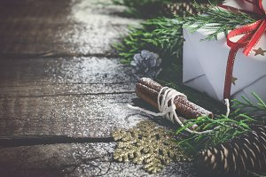 Vintage Christmas gift and coniferous Branches on an old wooden background. Toned