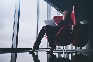 Woman is relaxing office on armchair