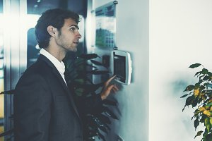 Businessman tuning terminal on wall