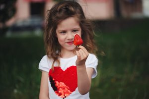 beautiful girl eating big juicy strawberry