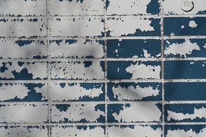 Blue & white paint peeling off brick