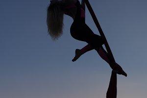 Woman acrobat dances on on canvases.