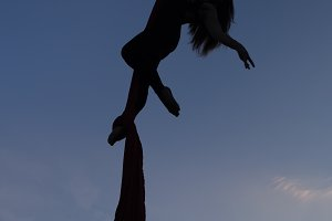 Aerial yoga on a sky background silhouette.