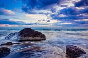 waves and rocks on beach of sunset