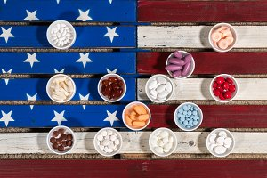 Multiple containers of prescription drugs on USA flag
