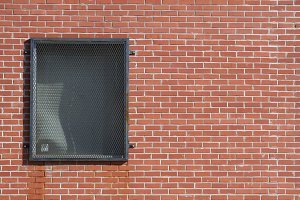 Metal Grated Window in Brick Wall