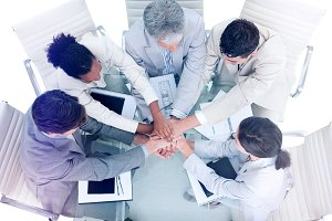 Cheerful international business people with hands together