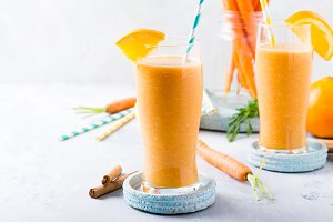 Healthy carrot smoothie with orange and cinnamon in glass