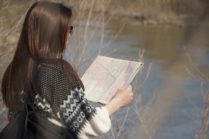 Beautiful woman stands near the river with a map in the hands