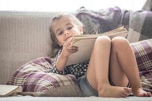 little girl reading book on sofa