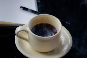Cup of coffee with book & pen