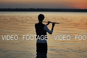 silhouette of a flutist playing in the sunset standing in the water