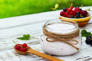 Yogurt in a jar and a saucer with berries on a table in the fresh air