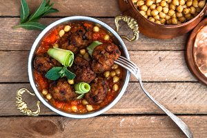 Arabian meatballs kofte with chickpeas, spicy tomato sauce and mint