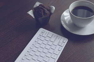 Keyboard, coffee and muffin