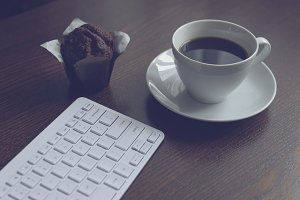 Keyboard, coffee and muffin