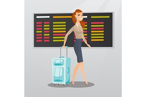 Caucasian woman walking with suitcase at airport.