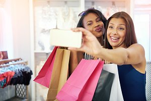 Playful young women shoppers posing for a selfie