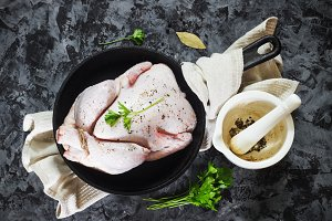 Raw chicken on a cast-iron frying pan on a black concrete background