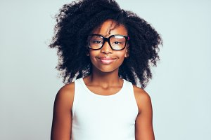 Cute youing African girl wearing glasses against a gray background