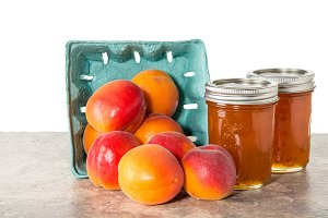 Box of apricots with jars of jam