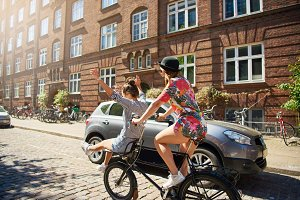 Laughing girlfriends riding a bicycle together through the city
