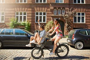 Carefree girlfriends riding a bicycle together through the city