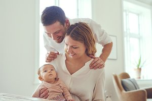 Smiling mother and father with their baby daughter at home