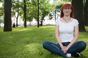 Woman in glasses sitting on grass in summer park