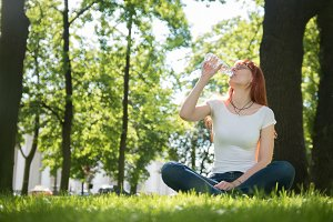 Woman in glasses sitting on grass in summer park and drinks water