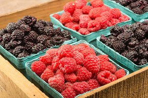 Crate with red and black raspberries