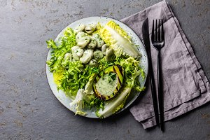 Vegetarian lettuce beans salad with grilled avocado and herb sauce. Top view
