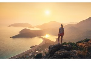 Landscape with girl, sea, mountain ridges and orange sky