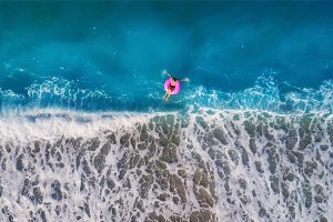 Aerial view of young woman swimming on the pink swim ring