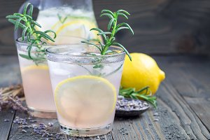 Homemade lemonade with lavender, fresh lemons and rosemary on wooden table, horizontal, copy space