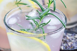 Homemade lemonade with lavender, fresh lemons and rosemary on wooden table, vertical, closeup